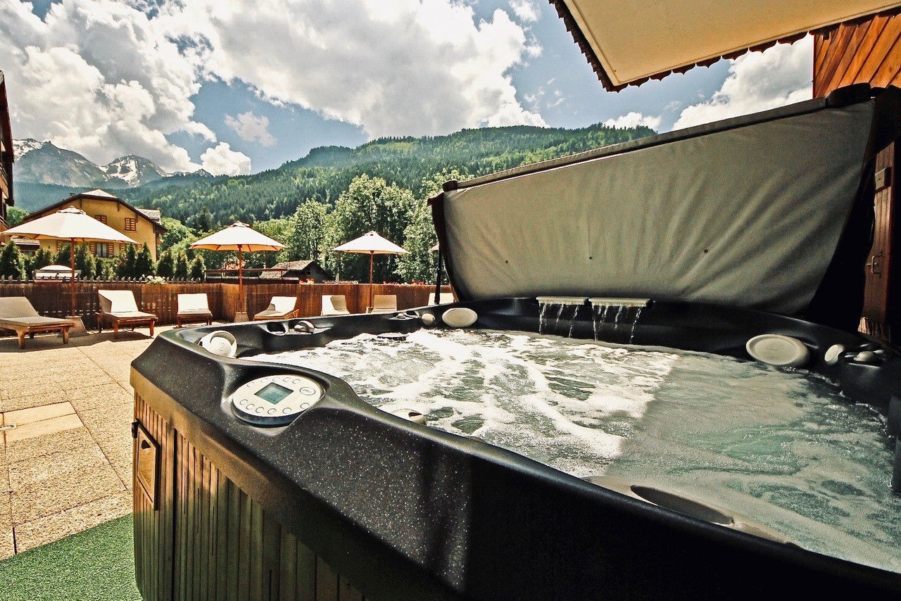 Jacuzzi and solarium on a sunny day, overlooking the Aravis Mountains